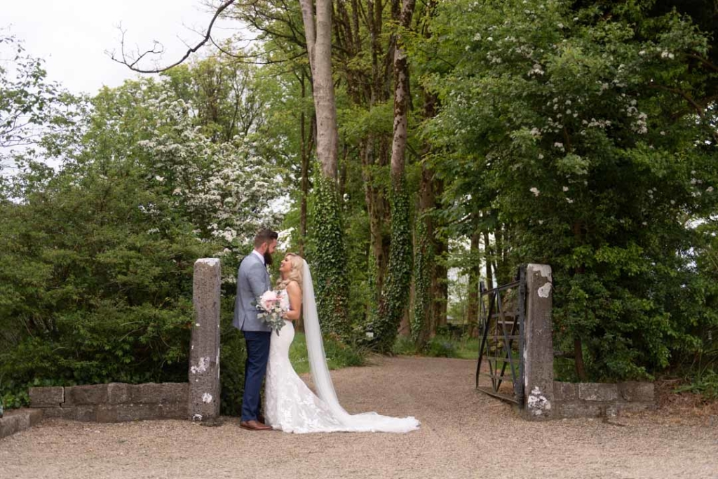 Bride and groom standing at the gates into the gardens at Clonabreany House wedding venue