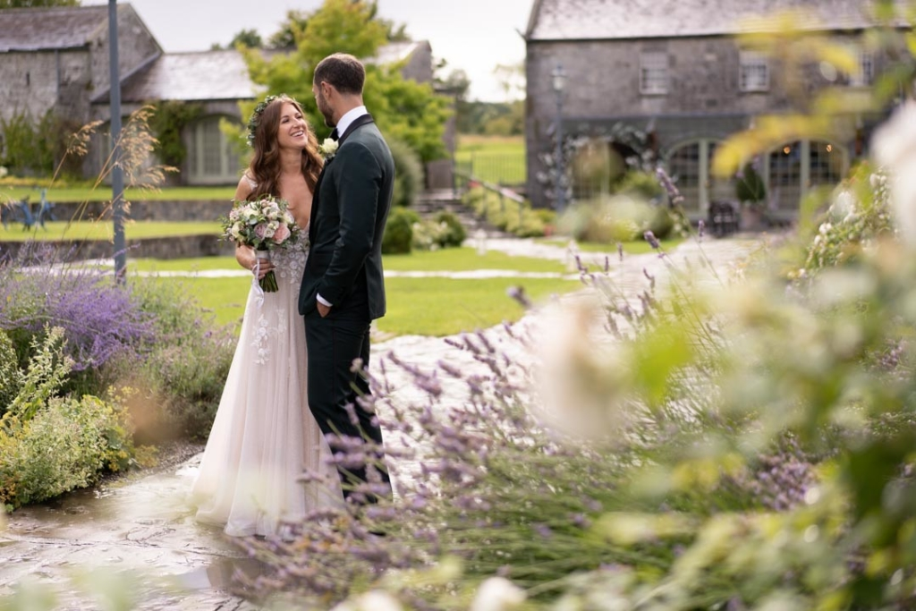 Bride and groom standing and laughing together in the gardens of Ballymagarvey Village