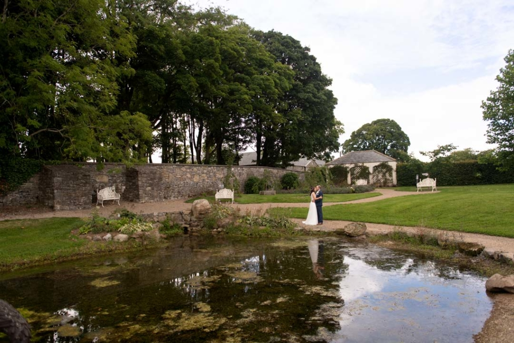 Bride and groom standing beside the lake at the Clonabreany wedding venue in Ireland