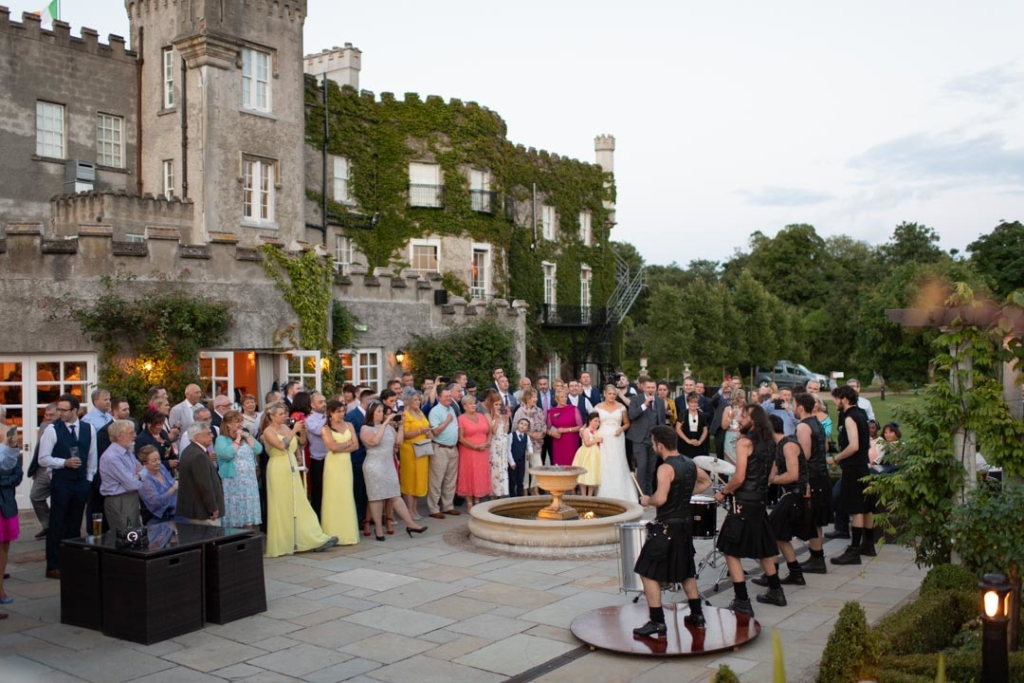 Wedding guests outside of Bellingham Castle being entertained by the musicians