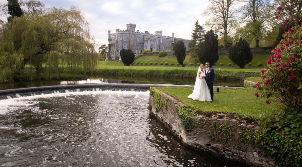 Bride and groom standing beside the river with Bellingham Castle behind them