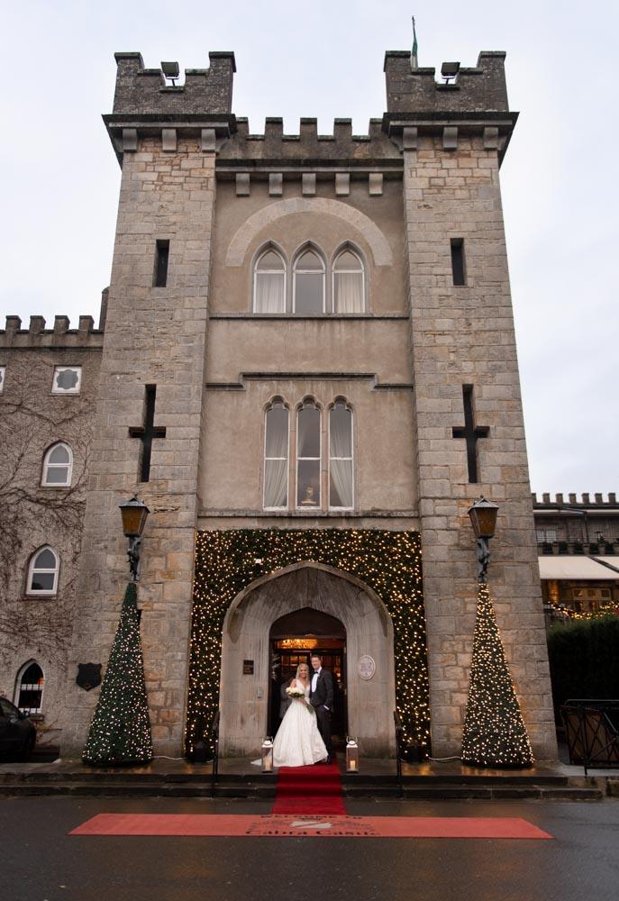 Bride and groom at the entrance of the Cabra Castle wedding venue in Ireland