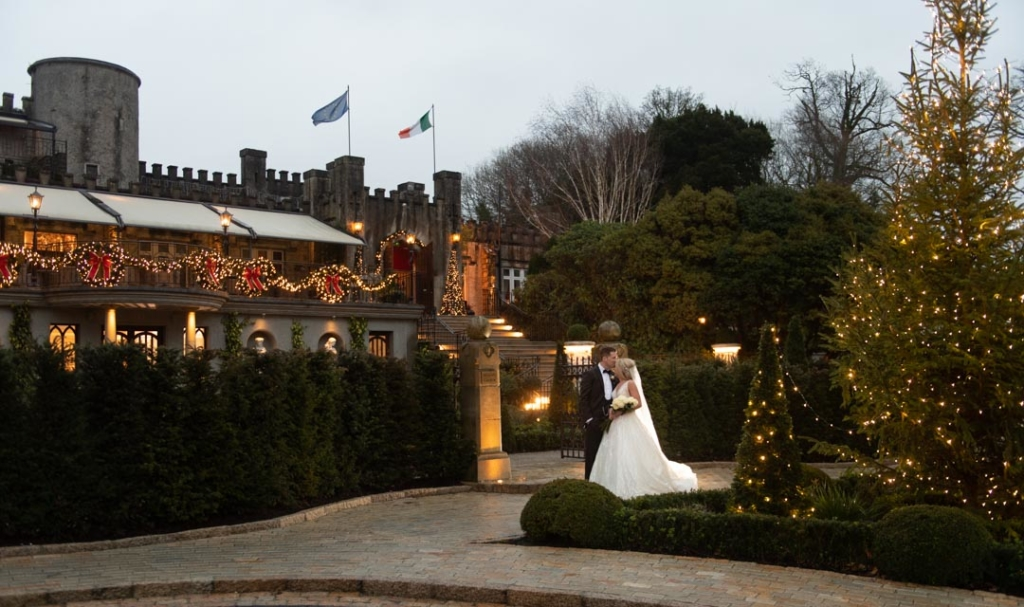 Bride and groom kissing on the grounds of Cabra Castle wedding venue with Christmas lights on the trees