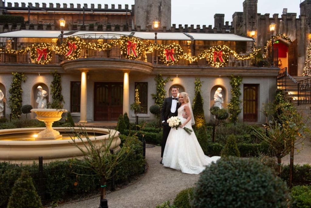 Bride and groom standing beside the fountain at Cabra Castle with Christmas lights and big red bows in the background