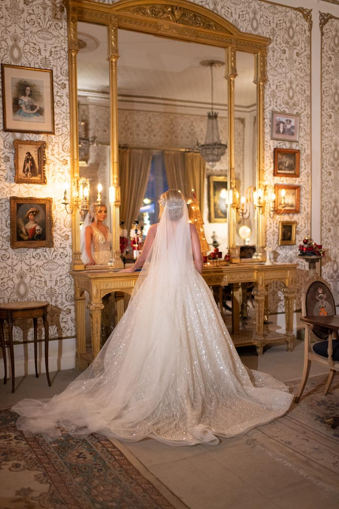 Bride standing and looking in the mirror in the gold room at the Cabra Castle wedding venue