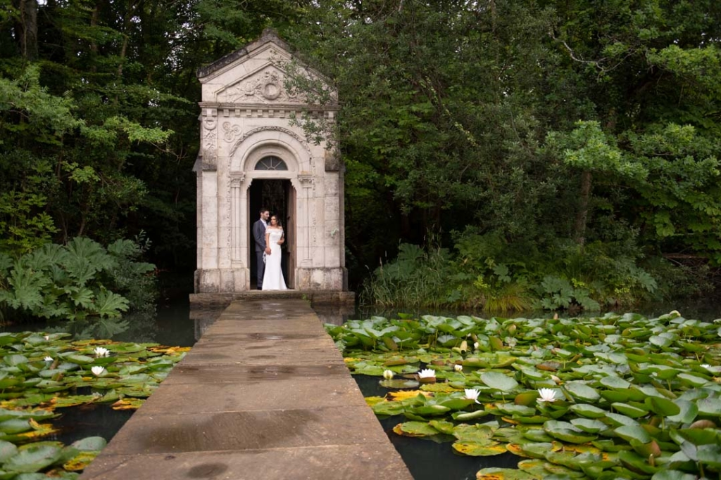 Bride and groom standing beside the lake, covered with lilies, at the Cliff at Lyons