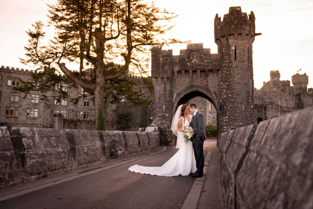 Bride and groom embracing on the bridge in front of the Ashford Castle hotel in Ireland