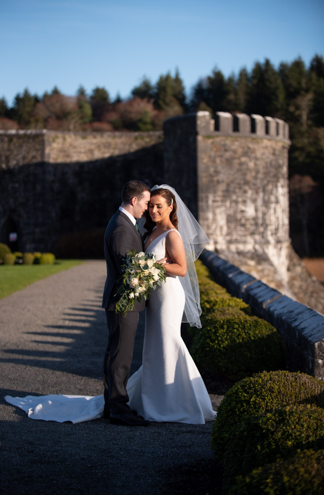 Bride and groom embracing in the grounds of the Ashford Castle hotel at golden hour