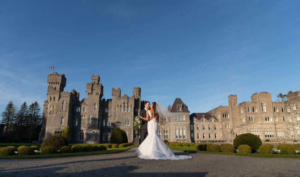 Bride and groom embracing in front of the grounds of the Ashford Castle hotel in Ireland
