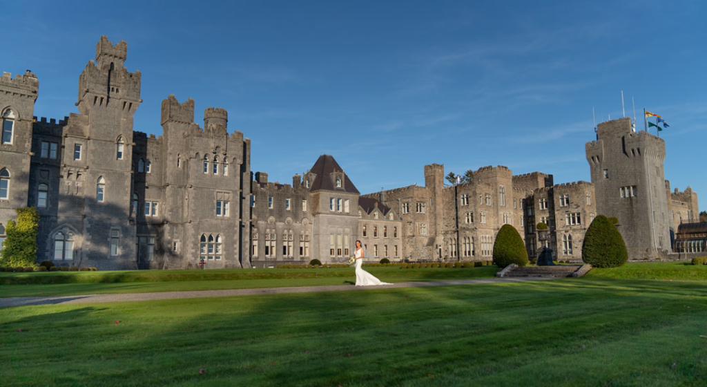 Bride standing in front of Ashford Castle hotel one of the top wedding venues in Ireland