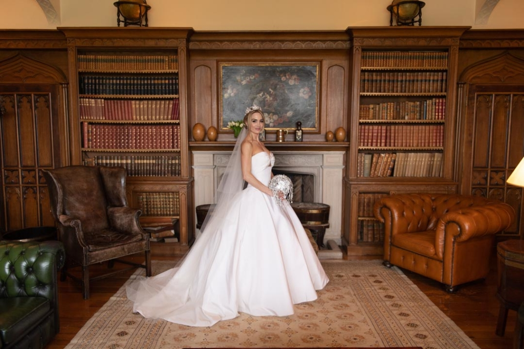 Bride standing in her wedding dress in the library at the Luttrellstown Castle in Ireland