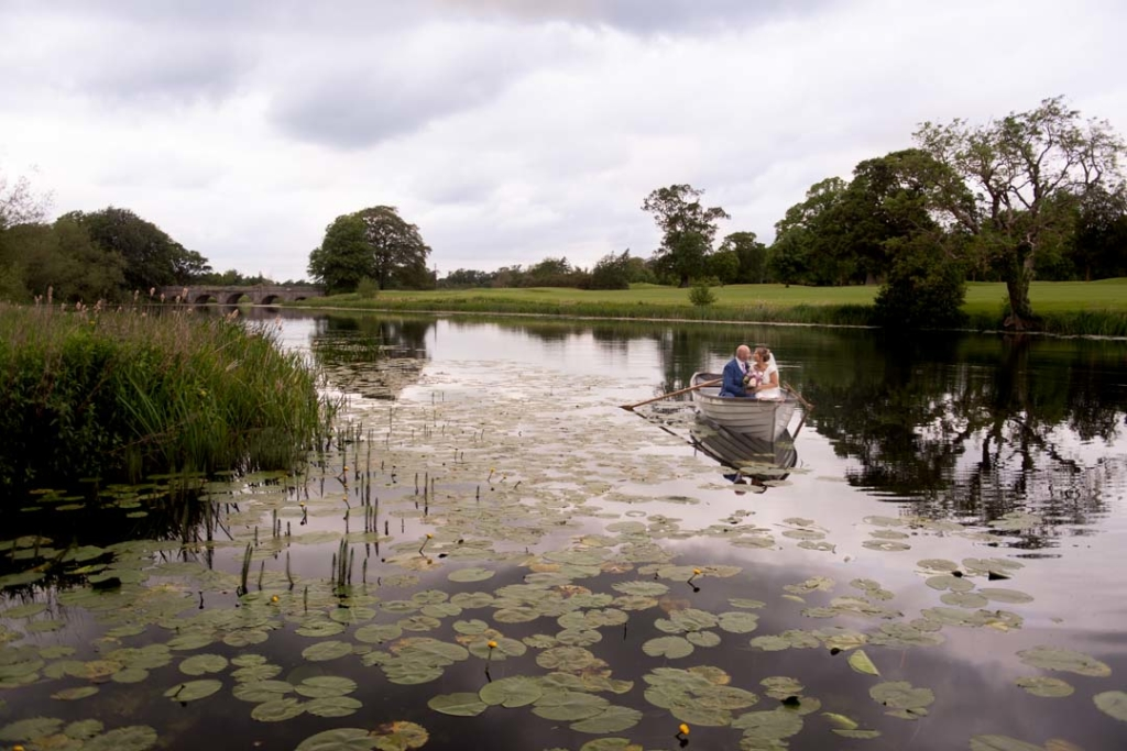 Bride and groom in a boat on the lake at Luttrellstown Castle wedding venue in Ireland