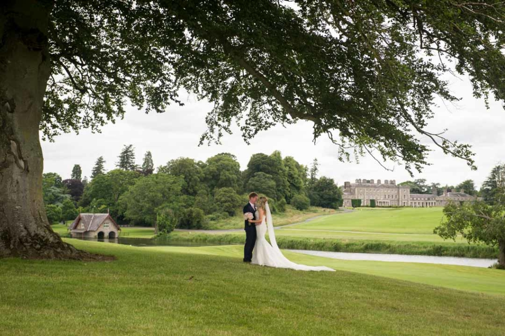 Bride and groom embracing under the tree on the grounds of Carton House in Ireland