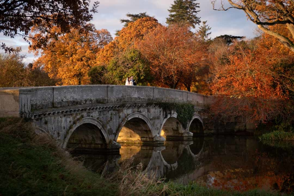 Bride and groom standing on the bridge surrounded by autumn trees at Carton House in Ireland
