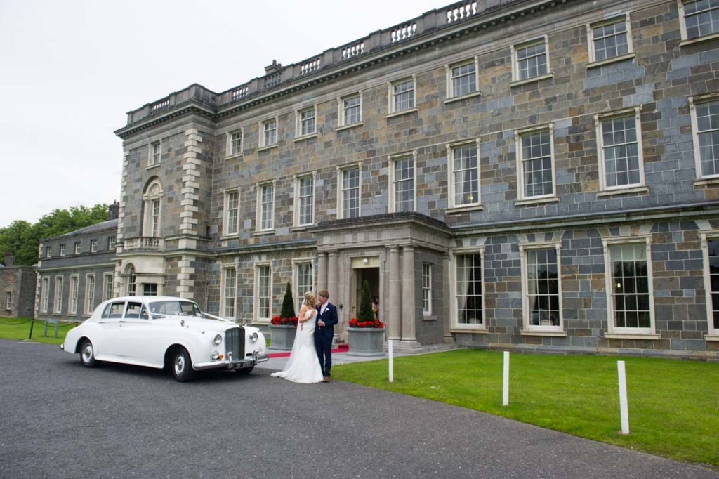 Bride and groom standing beside their white vintage wedding car in front of Carton House Hotel
