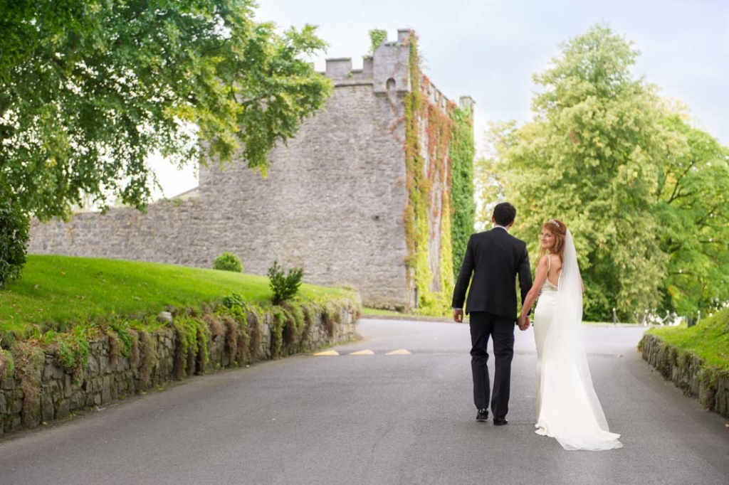 Bride and groom walking holding hands with the Bride looking back over her shoulder with Castle Durrow in the background