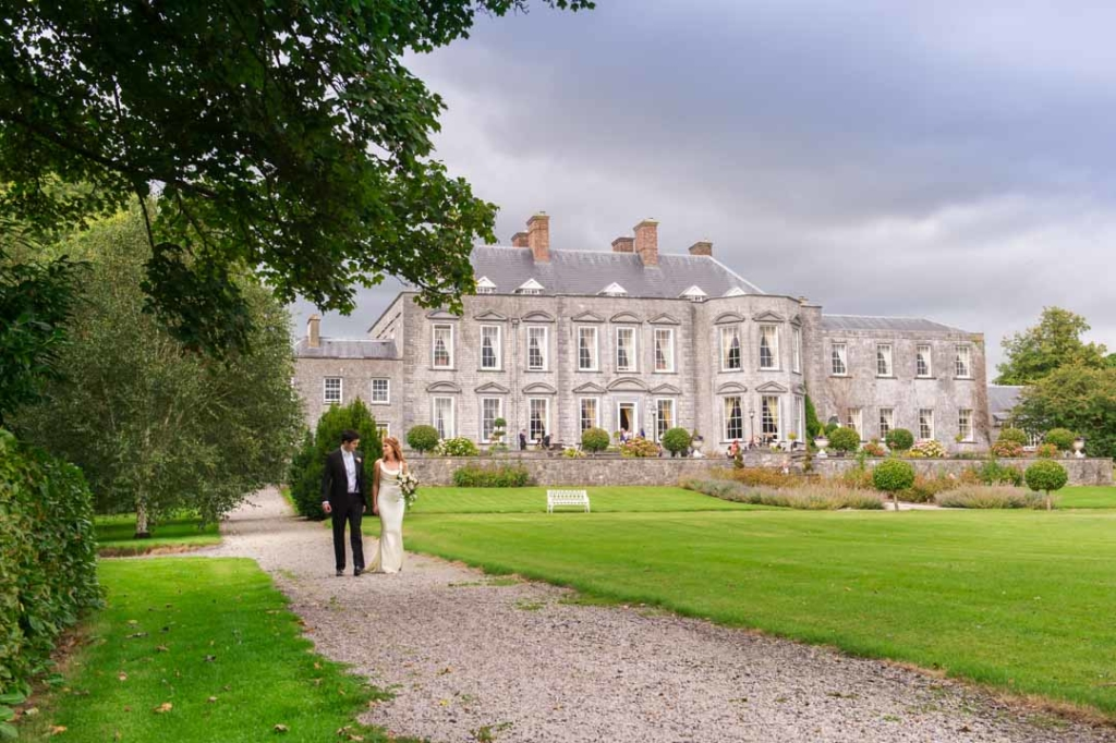 Bride and groom walking together in the grounds of Castle Durrow in Ireland