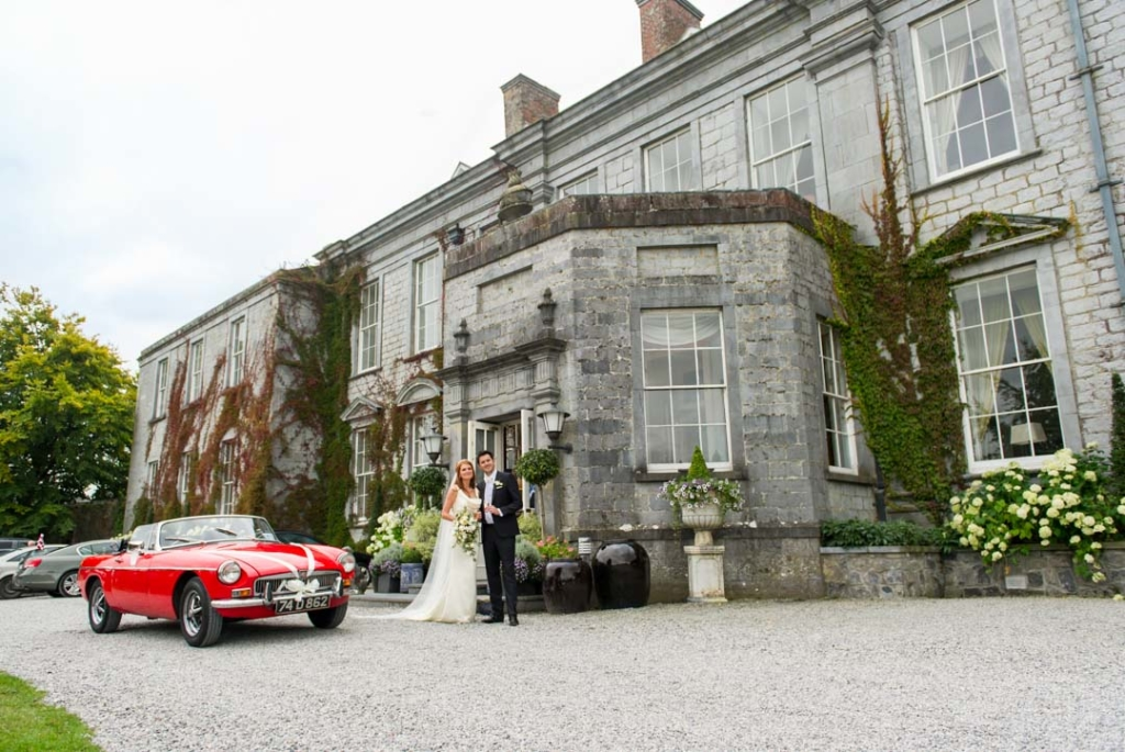 Bride and groom standing beside their red mg wedding car in front of Castle Durrow