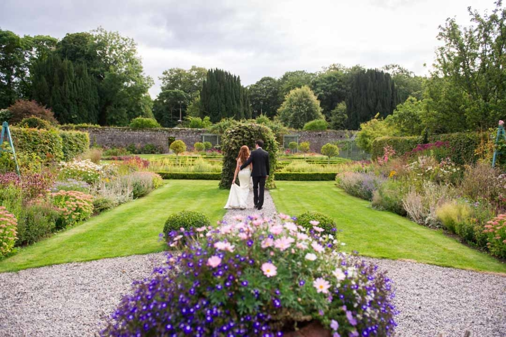 Bride and groom walking together through the grounds of Castle Durrow in Ireland