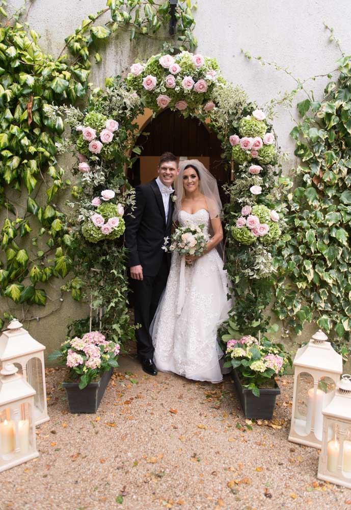 Bride and groom standing in the arch surrounded by flowers at the chapel in the Brooklodge wedding venue