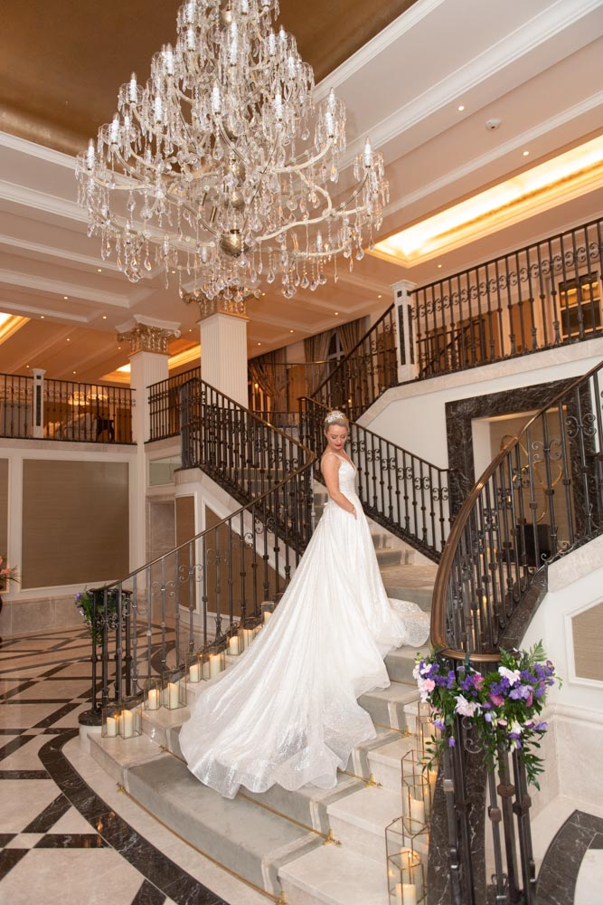 Bride standing on the stairs under the chandelier at the Adare Manor hotel top wedding venues in Ireland