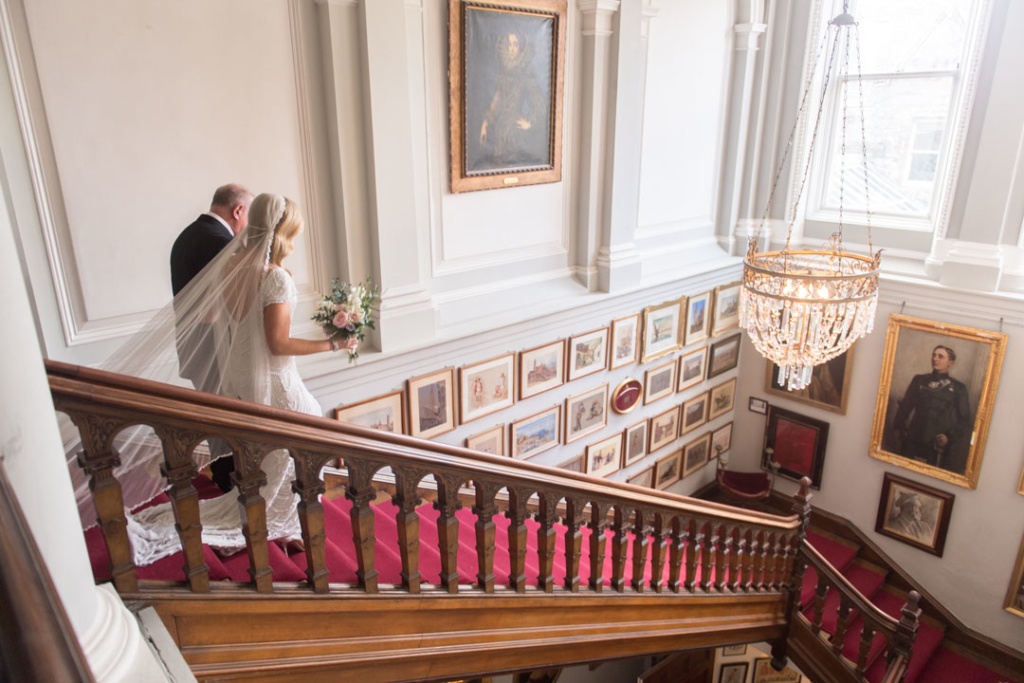 Bride and her dad walking down the stairs at the Castle Leslie wedding venue