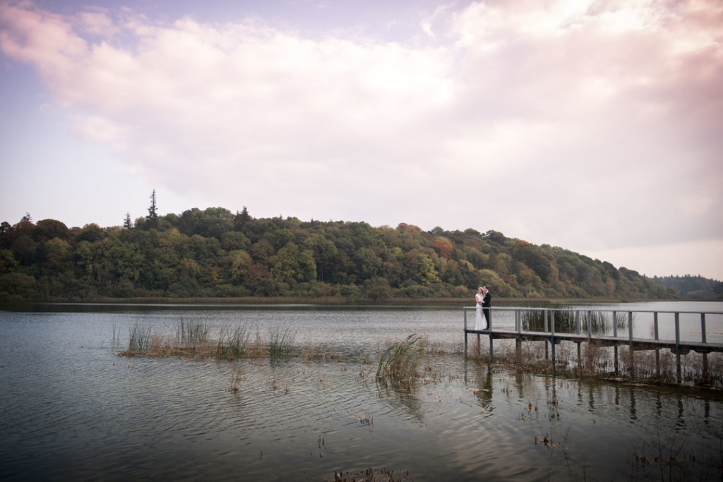 Bride and groom standing on the boardwalk at the lake at Castle Leslie in Ireland