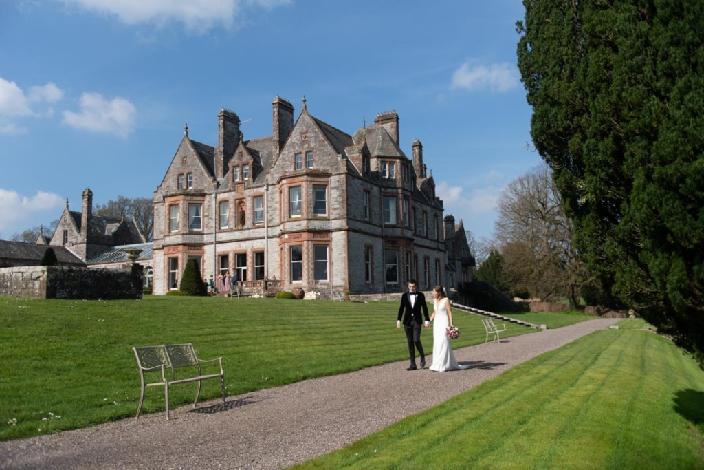 Bride and groom walking together with Castle Leslie wedding venue in the background