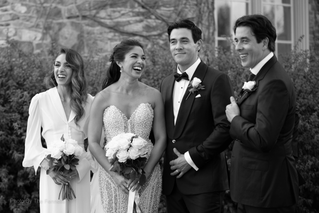 Sarah Roberts and James Stewart laughing together with their bridesmaid and groomsman