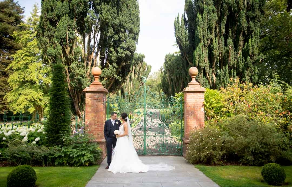 Bride and Groom standing in front of green gates at Tankardstown House