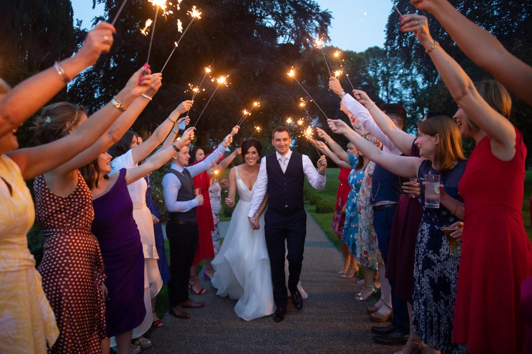 Groom leading Bride through a tunnel of sparklers with their guests
