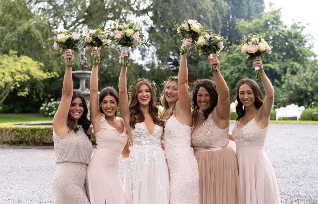 Bride and Bridesmaids laughing with their flowers held over their heads