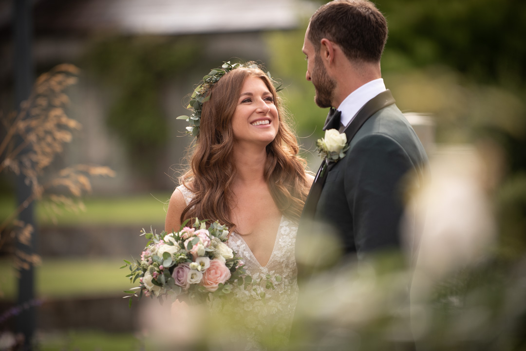 Bride and Groom smiling and looking at each other at Ballymagarvey Village
