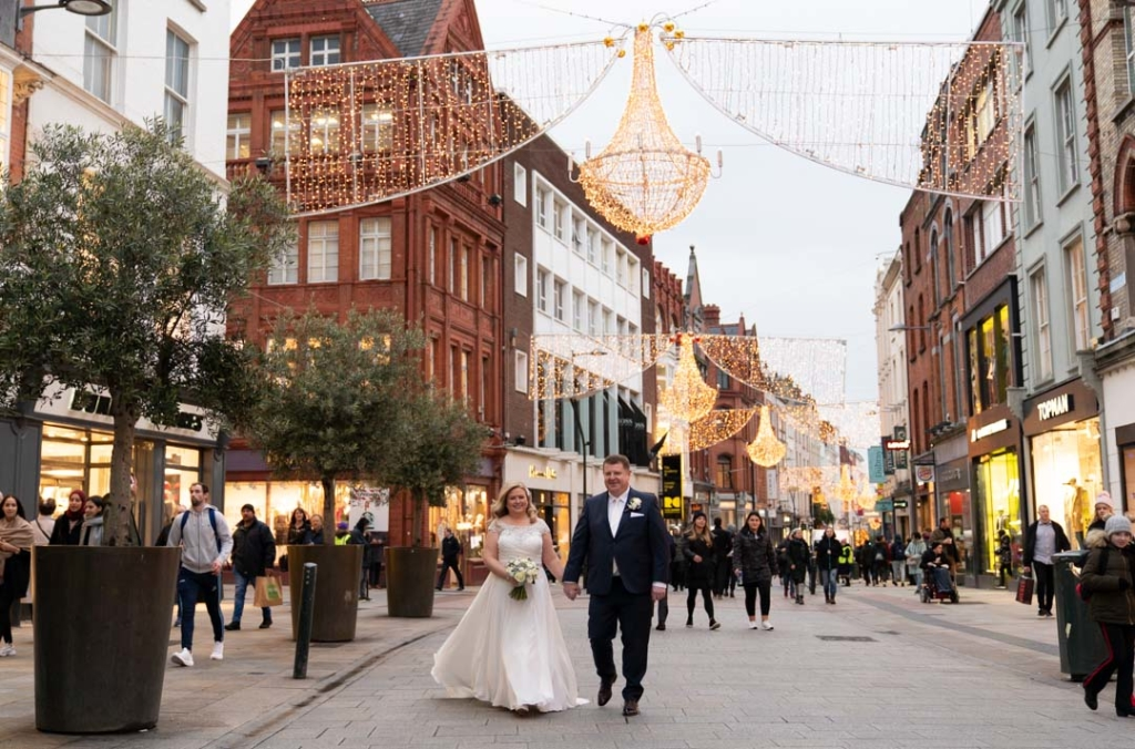 Bride and groom walking on Grafton Street with the Christmas lights on