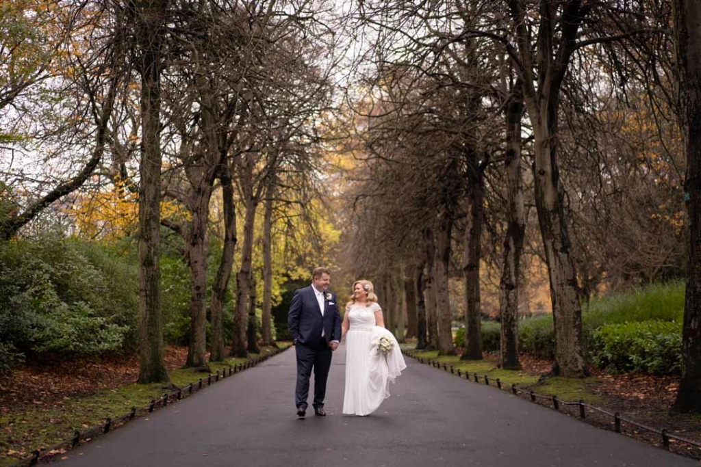 Bride and groom holding hands walking in St.Stephens Green park