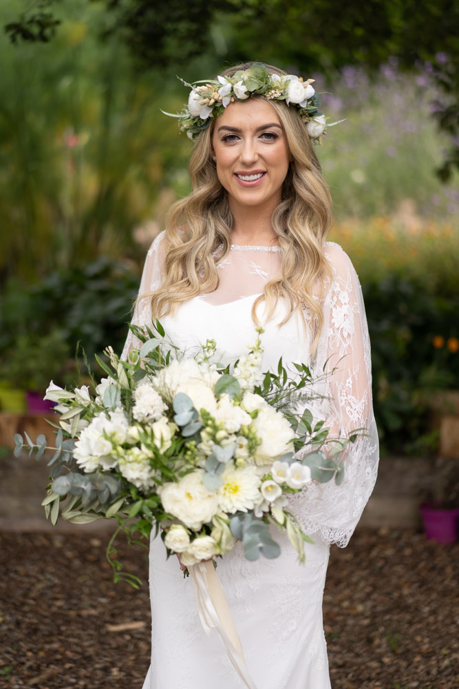 The Bride in her wedding dress and white flower crown on her head holding her flower bouquet