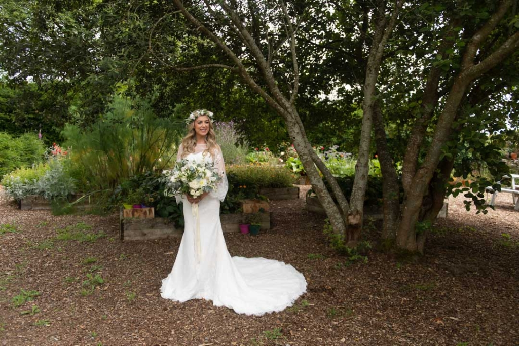 Bride standing in the garden at Mount Druid in her wedding dress
