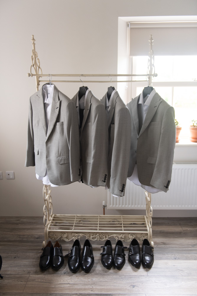 The Groom and groomsmen grey suits on the hangers and their black shoes on the floor