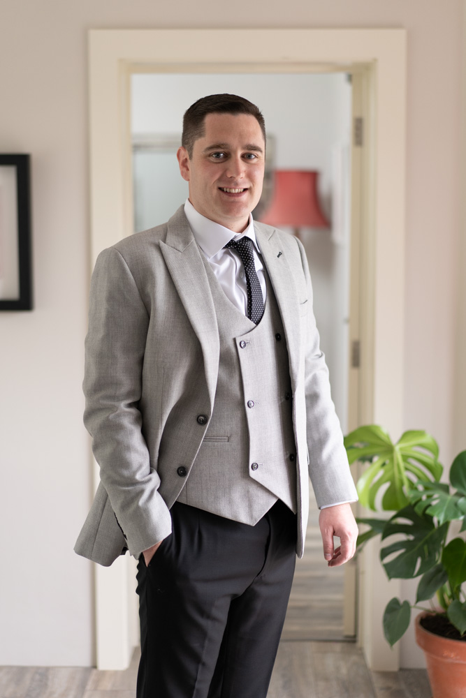 Groom in his three piece grey wedding suit
