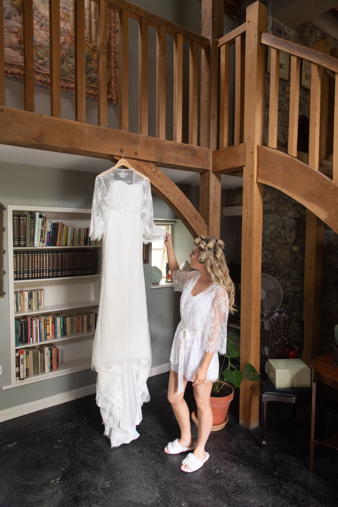Bride standing in her bridal dressing gown looking at her wedding dress