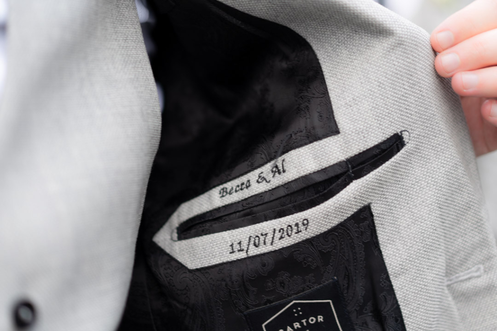 The inside of the grooms wedding jacket with his name and his wife name and wedding date embroidered on it