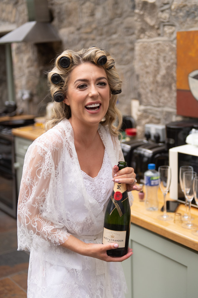 Bride laughing holding a bottle of Moet Champagne