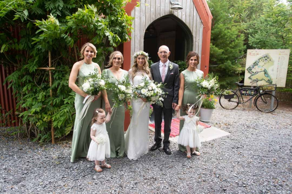 Bride and her dad and Bridesmaids standing outside the entrance to the Tin Chapel at Mount Druid