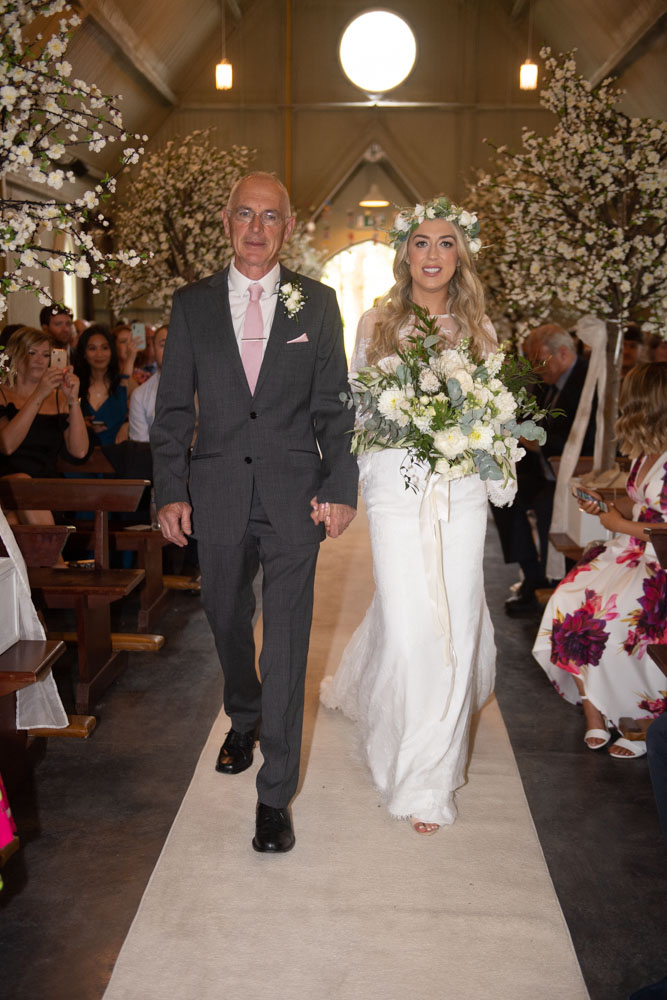 Bride and her dad walking up the aisle at Mount Druid