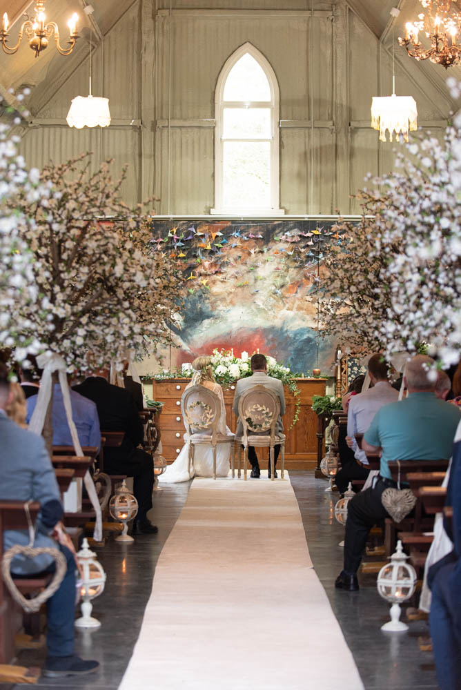 Bride and Groom sitting at the top of the aisle surrounded by cherry blossom trees in the Tin Chapel for their Mount Druid wedding