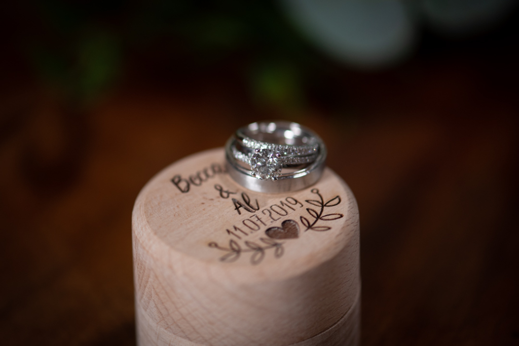 Diamond engagement ring with his and hers wedding bands sitting on the ring box with their names engraved on the box