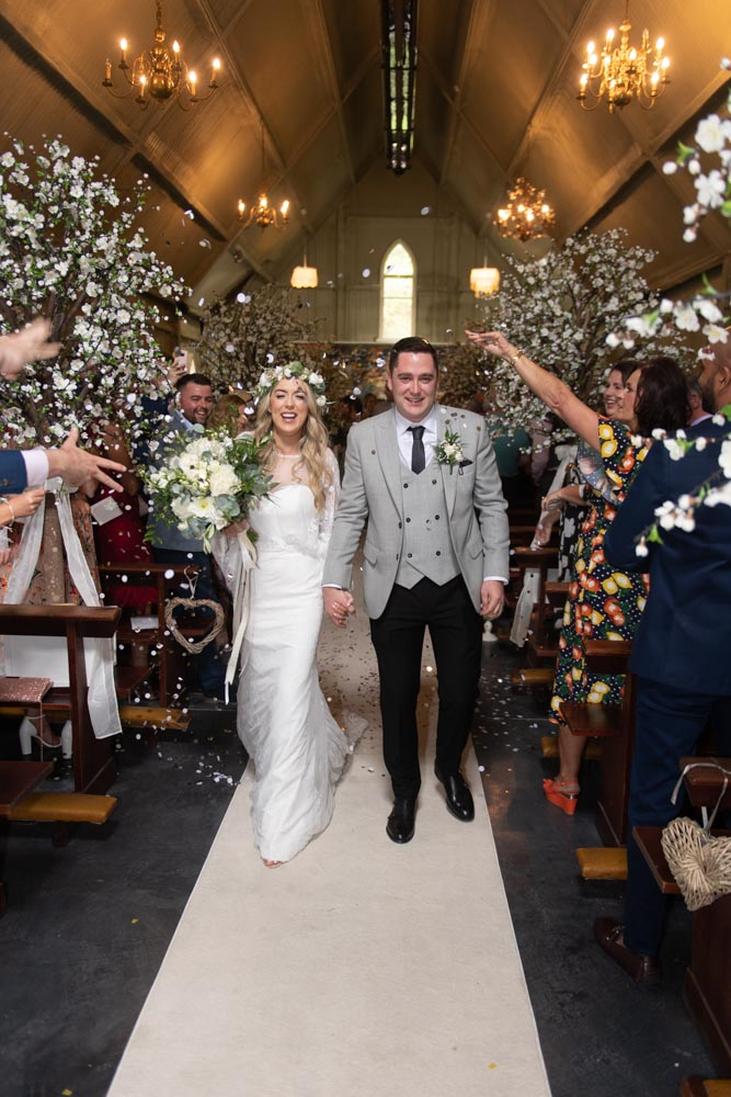 Bride and Groom walking down the aisle while their guests throw confetti over them