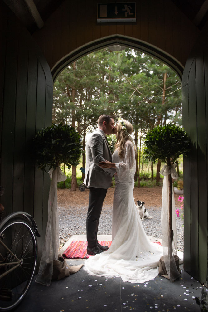 Silhouette photo of Bride and Groom kissing in the doors of the Tin Chapel at Mount Druid