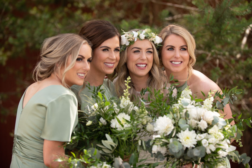 Bride and her Bridesmaids together holding flowers and smiling