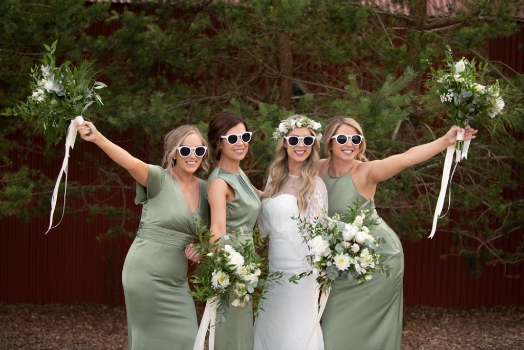 Bride and her bridesmaids wearing sun glasses and holding their flower bouquets in the air